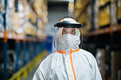 Worker with protective mask and suit in industrial factory, looking at camera.