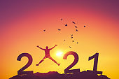 Silhouette man jumping and birds flying on sunset sky at top of mountain and number like 2021 abstract background.