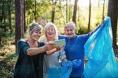 Senior women friends picking up litter outdoors in forest, taking selfie.