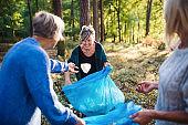 Senior women friends picking up litter outdoors in forest, a plogging concept.