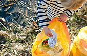 Unrecognizable small child collecting rubbish outdoors in nature, plogging concept.