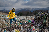 Woman with gas mask walking on landfill, environmental concept.