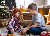 Small girl and boy in pajamas indoors at home at Christmas, playing board games.