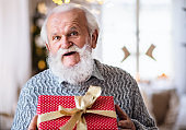 Front view of happy senior man with present box indoors at home at Christmas.