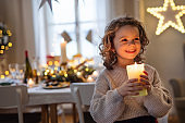 Cheerful small girl standing indoors at Christmas, holding candle.