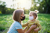 Side view of happy mother talking to small daughter in nature, wearing face masks.