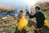Father with small kids collecting rubbish outdoors in nature, plogging concept.