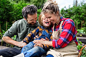 Family with small child having fun on farm, growing organic vegetables.