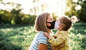 Side view of happy mother kissing small daughter in nature, wearing face masks.