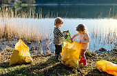 Small children collecting rubbish outdoors in nature, plogging concept.