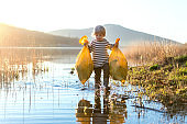 Small child collecting rubbish outdoors in nature, plogging concept.