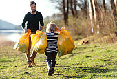 Father with small son collecting rubbish outdoors in nature, plogging concept.