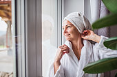 Portrait of woman with bathrobe and towel on head standing indoors.