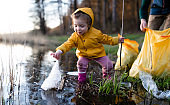Father with small daughter collecting rubbish outdoors in nature, plogging concept.