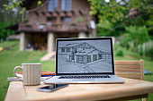 Laptop with blueprints on desk outdoors in garden, home office concept.