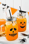 Halloween pumpkin iced mocktails in glass jars decorated with scary faces on a white table. DIY Halloween Party decoration on the wall.