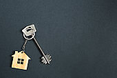 Key chain in the shape of wooden house with key on a black background. Building, design, project, moving to new home, mortgage, rent and purchase real estate. Copy space