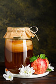 Homemade fermented kombucha in a glass jar and fresh apples on a rustic background. A healthy probiotic drink.