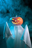 Halloween concept. A ghost with a creepy head glowing jack-o-lantern pumpkin stands in the fog at dusk.