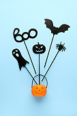 Happy Halloween day background. Top view Halloween party accessories and Jack-O-lantern pumpkin on pastel blue background.