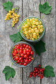 Red and white currants in glass jars. Eco food concept.