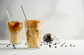 Two glasses of iced coffee on a light concrete table.