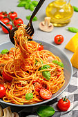 Italian pasta with tomato sauce, cherry tomatoes, mushrooms and basil on a gray concrete table.