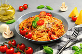 Spaghetti with tomato sauce, cherry tomatoes, mushrooms and basil in a plate on a gray background. Traditional Italian food.