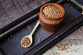 Dry buckwheat in a clay pot on a dark wooden tray.