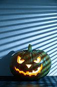 Halloween holiday background. Spooky Halloween pumpkin on the table, illuminated by moonlight through the jalousie.