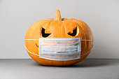 New normal concept. Halloween pumpkin in a protective medical mask on a gray background.