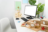 Christmas Shopping online with a credit card. Christmas gifts and a computer monitor on a table in a home office.