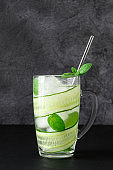 Detox cold drink with sliced cucumber and mint leaves in glasses.