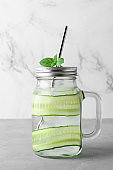 Refreshing cocktail with cucumber slices, mint leaves and ice cubes in jar. Light gray concrete table.