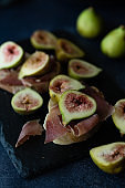 Bread with ham and fresh figs served on a black stone plate.