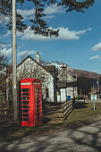 Red telephone box on a side of a road in the countryside in the UK