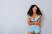 Happy young african american woman laughing against gray background with arms crossed