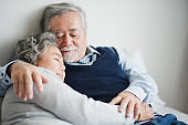 Senior Asian couple love lying on the bed with hug and hold the hand. Retired man and woman sleeping with talking on bed in bed room at home which smiling and felling happy. Old couple love concept