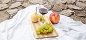 Picnic in the nature in the park. A glass of wine green grapes yellow pear red apple lilac on a wooden board on a white tablecloth in the grass in the garden on a stone path.