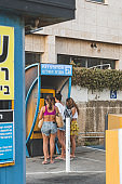 Young women paying for parking, using ticket machine on a car parking in Tel Aviv, Israel