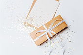 Gift and blank note with envelope, gold glitter stars on white background