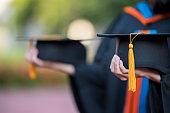 closeup of female graduates, university graduates, holding a black hat