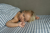 One year cute blond baby sleeps, raising hands up, on white and blue sheets. View from a side, good background, copy space.