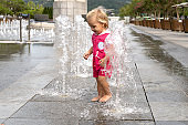 Cute small caucasian baby kid playing at fountain at summer day, good weather, childhood concept, copy space.