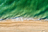 The scenic sea of green color with waves and sandy shore. Aerial view.