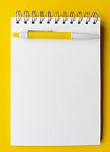 Blank sheet of notebook with pen on it. Educational concept in yellow and white colors. Stock photography.