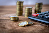 A stack of coins and a calculator on a wooden table. Concept of savings and financial accounting. Selective focus.