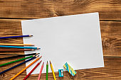 A blank sheet of paper with colored pencils on a wooden table . Close up.