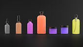 Set of body care flasks with abstract liquid on dark background.