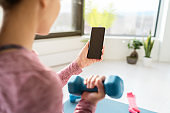 Home workout phone app woman using cellphone to watch training videos online following personal trainer coach for weight loss exercises lifting weights.